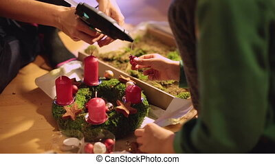 Mother making an advent wreath with child, christmas spirit