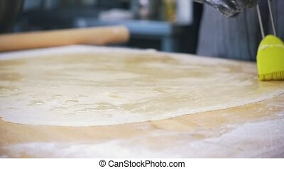 Making apple strudel - raw dough for cake smeared with oil,...