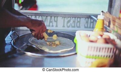 Making banana pancake on the street of Samui by the beach....