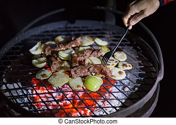 Making barbeque at night. Human hand holding fork arranging sausages, potatoes and onions on grill. Braai, outdoors activity in South Africa.