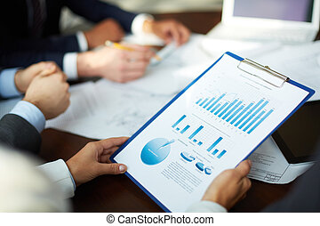 Image of business document held by human at meeting