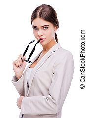 Making business look beautiful. Confident young businesswoman holding glasses near her lips and looking at camera while standing against white background