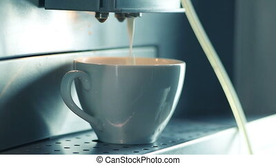 Making cappuccino in coffee maker. Closeup