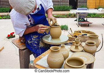 Making Clay Pot - MILAN, ITALY - MAY, 20: Pottery maker uses...