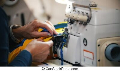 Making clothes. Female hands work on Sewing Machine at...
