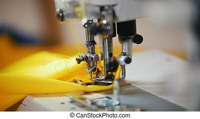 Making clothes. Female hands work on Sewing Machine. Close...