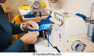 Making clothes. Woman works with cloth on Sewing Machine. 4K...