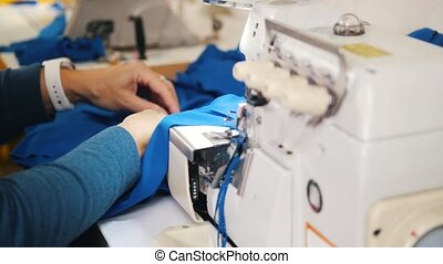 Making clothes. Woman works with cloth on Sewing Machine....