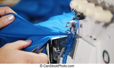 Making clothes. Woman works with textile on Sewing Machine....
