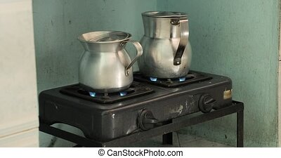 Heating milk and water for making coffee on an old metal stove in metal jugs