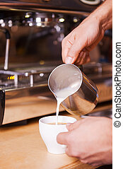 Making coffee. Close-up image of male barista pouring milk into the coffee cup
