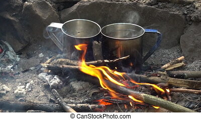 two cups in bonfire - making coffee or tea in traveling. two...