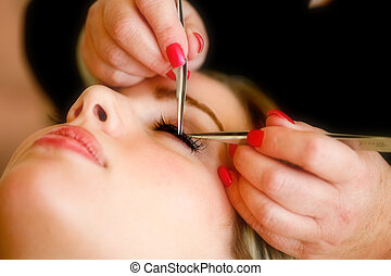 A pair of hands making eye lashes for a female