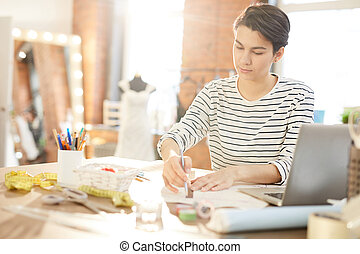 Young serious fashion designer in casualwear sitting by desk and making sketch for new collection