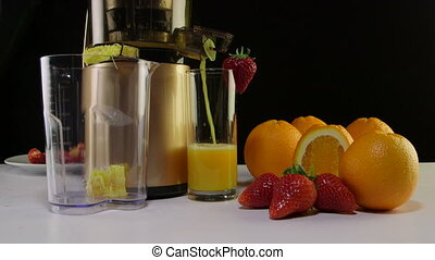 Making fresh fruit juice from strawberry and orange using masticating juicer