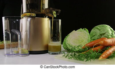 Making freshly squeeze juice from carrot and cabbage using cold press juicer