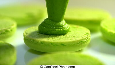 Making green pistachio macarons, squeezing and adding cream...