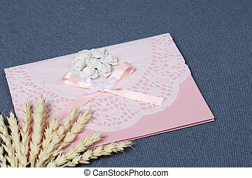 Making greeting card from paper, cardboard and tape. Near the surface are decorative accessories.