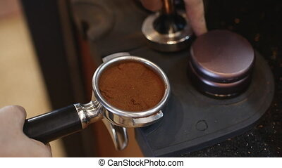 Making Ground Coffee with Tamping fresh coffee. Close-Up....