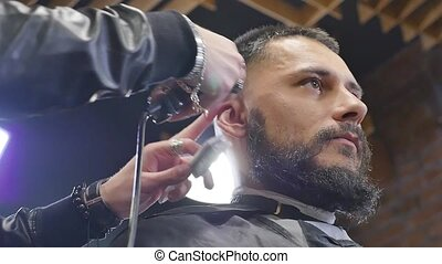 Making hair look magical. Young bearded man getting haircut...