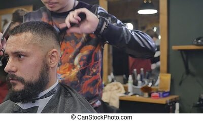 Making haircut look perfect. Young bearded man getting haircut by hairdresser while sitting in chair at barbershop slowmotion