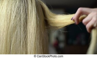 Making hairstyle for blonde young woman model