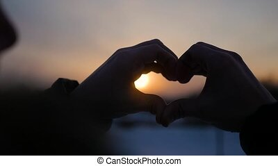Making heart with hands in the sun. Silhouette hand in heart shape with inside the sunset. Winter
