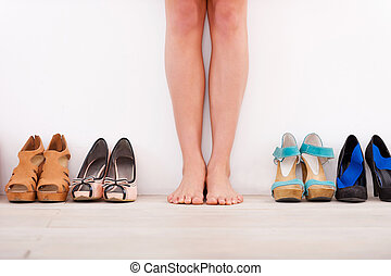 Making her choice. Cropped image of young woman standing against the wall while different shoes laying in a row near her