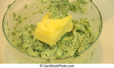 Making herb butter by adding soft butter to fresh herbs and...