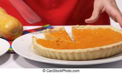 Making homemade pumpkin pie with fresh pumpkin. Woman cuts a piece of pie