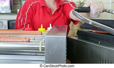 Making hotdogs in fast food lunch dinner - Female employee...