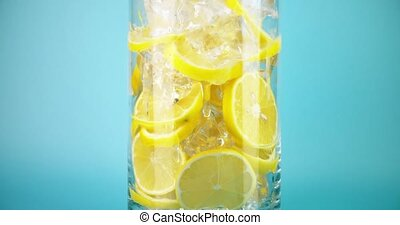 Making ice cold lemonade in a big glass, close-up slow ...