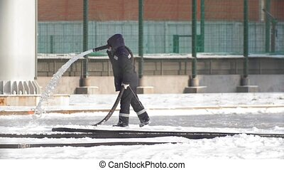 Making ice skating - personal pouring water from a hose and creates an ice skating rink
