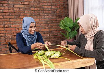making ketupat traditional indonesian food together for eid...