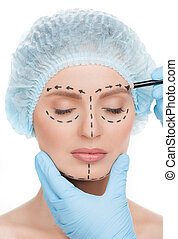 Making marks on face. Close-up of beautiful young woman in medical headwear keeping eyes closed while doctors hands in gloves making marks on her face isolated on white