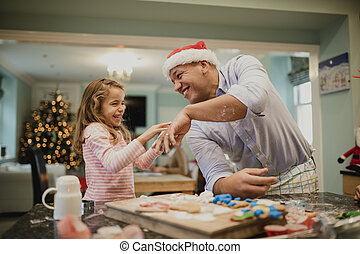 Making Messy Christmas Biscuits With Dad - Little girl is...