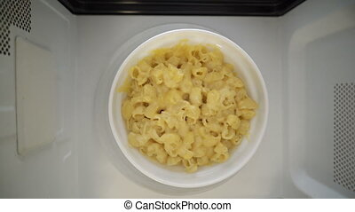 Making microwave meal. Macaroni and cheese in bowl...