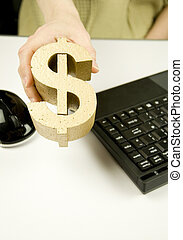 making money, woman holding gold dollar symbol in office with keyboard and mouse
