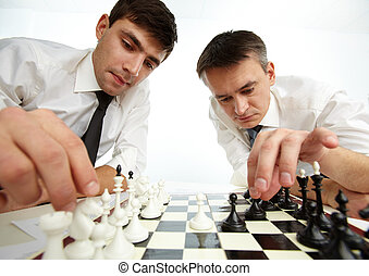 Making move - Two men looking at chess figures while making...