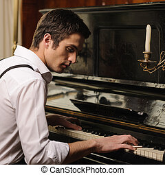 Making music. Profile of a handsome young man playing piano