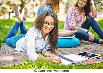 Making notes - Clever teenager making notes in park with her...