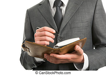 Making notes - Close-up of businessman holding notepad ready...