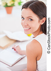 Making notes. Rear view of young beautiful woman writing something in her note pad and smiling at camera