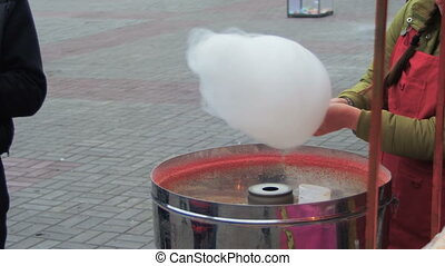 Making of Cotton Candy. Working woman making cotton candy...