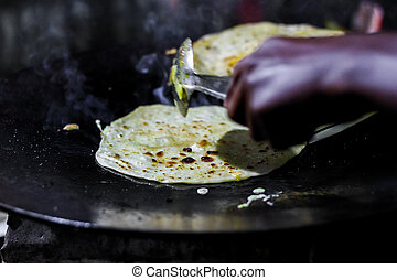 making of egg roll on a hot frying pan with oil and paratha ...