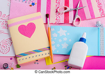 Making of greeting cards. Girl's workplace with scissors, glue, colored paper