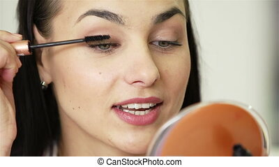 Making Oneself up - Extreme close up of young lady applying...