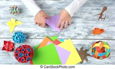 Making origami purple triangle. Wooden desk surface...