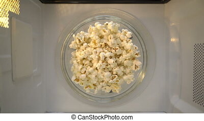 Bowl of popcorn turning around in microwave top view.