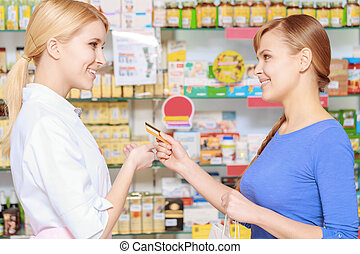 Making purchase in a drugstore - Payment with a card. Young...
